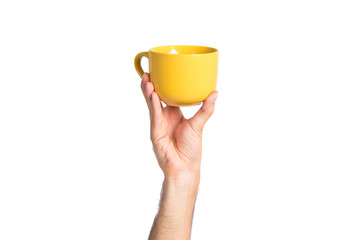 hand holding a yellow coffee cup over white