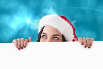 Pretty brunette in santa hat showing white poster