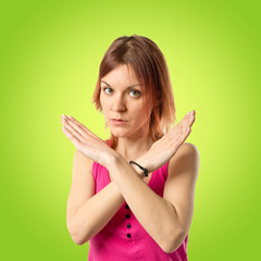 Redhead girl doing NO gesture over green background