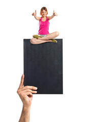 Pretty young girl with thumbs up sitting on book
