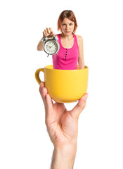 Serious redhead girl holding a clock inside cup of coffee