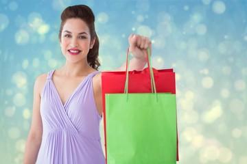 Portrait of pretty brunette showing shopping bags