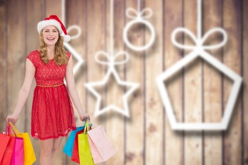 Pretty woman in santa hat standing with shopping bags