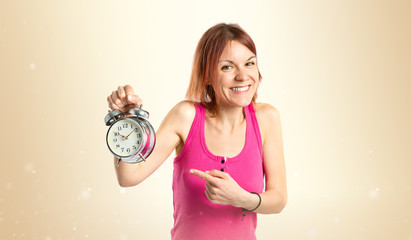 Happy redhead girl holding a clock over white background