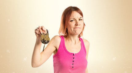 Redhead girl holding vintage padlock over white background