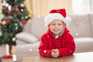 Composite image of festive little boy smiling at camera