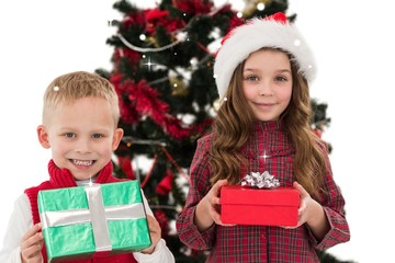 Festive little siblings smiling at camera holding gifts