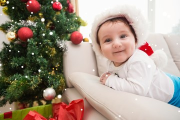 Composite image of cute baby boy on couch at christmas