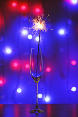 Beautiful sparkler in glass on shiny background, close up