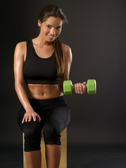 Smiling woman doing seated dumbbell curl