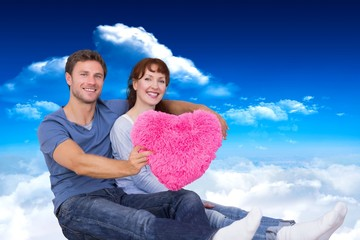 Composite image of couple holding a large heart