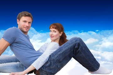Composite image of couple sitting on the floor
