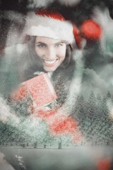 Composite image of festive brunette pressing gift at christmas