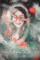 Happy little girl in santa hat holding candy canes