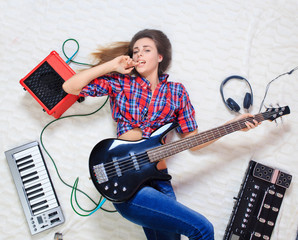 girl lying on the floor with bass guitar