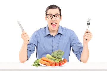 Cheerful man eating a bunch of vegetables