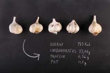 garlic cloves on dark chalkboard with copy-space