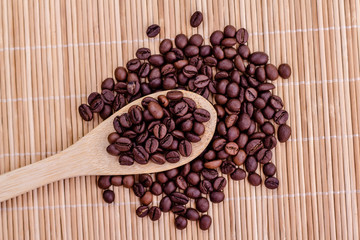 wooden spoon full of coffee beans