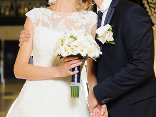 Groom Embracing Bride with Bouquet