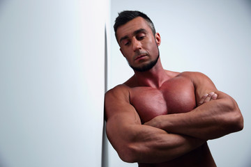 pensive muscular man with arms folded leaning