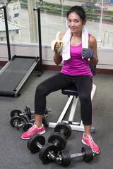 woman at the gym eating a banana