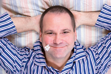 Happy man resting in bed