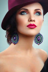 beautiful girl with makeup in hat and earrings