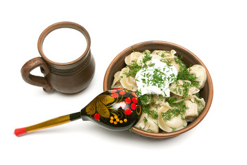 dumplings with fresh herbs and sour cream in a clay plate and cu