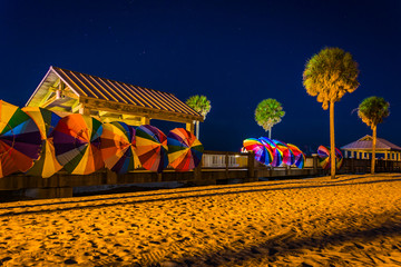 Palm trees and colorful beach umbrellas at night in Clearwater B