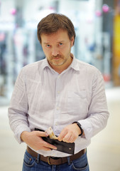 Stressed middle age man holding purse with russian paper money