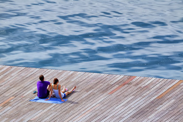 Rear view of loving teenage couple sitting on deck looking at vi