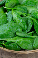 spinach in a basket on wooden surface