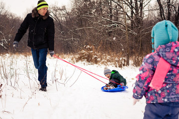 Image of adult pulling two children on a sled (concept: winter f
