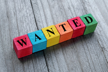 word wanted on colorful wooden cubes