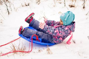 Girl in winter outdoors sledding