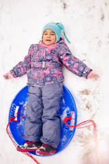 Girl in winter outdoors sledding