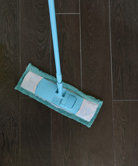 cleaning the tiled floor with blue mop