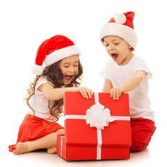Happy kids in Santa hat opening a gift box