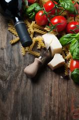 italian food with raw fusilli, tomato, basil, cheese