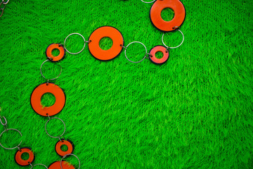 orange beads on a green knitted cloth