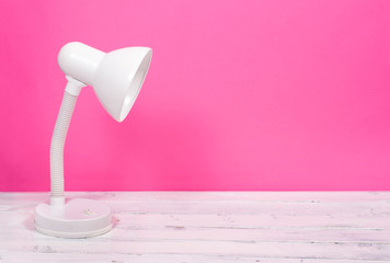 White lamp on white wood desk on pink background