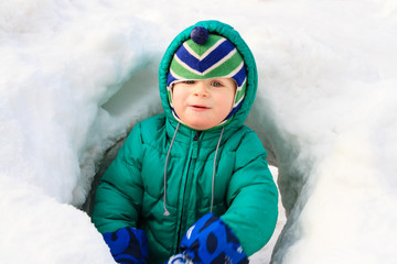 Little boy having fun in winter snow