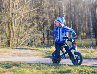 little boy on running bike in park