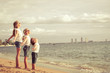Three happy children standing on the beach