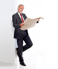Mature business man reading a newspaper, and being surprised