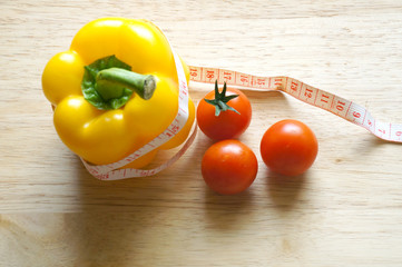 Yellow pepper bell with measuring tape and tomatoes