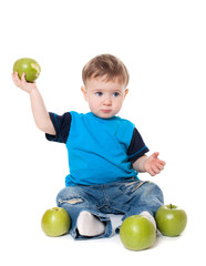 Cute baby boy kid eating and playing with green apples