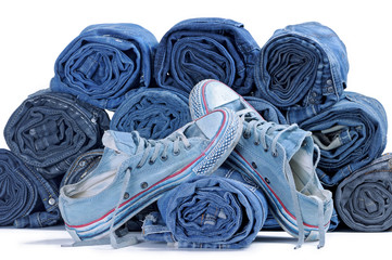 Pair of blue sneakers and stack of rolled colored jeans