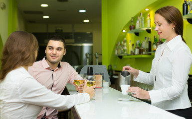 Female barista and two clients in cafe
