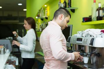 Bartender and barista working at bar